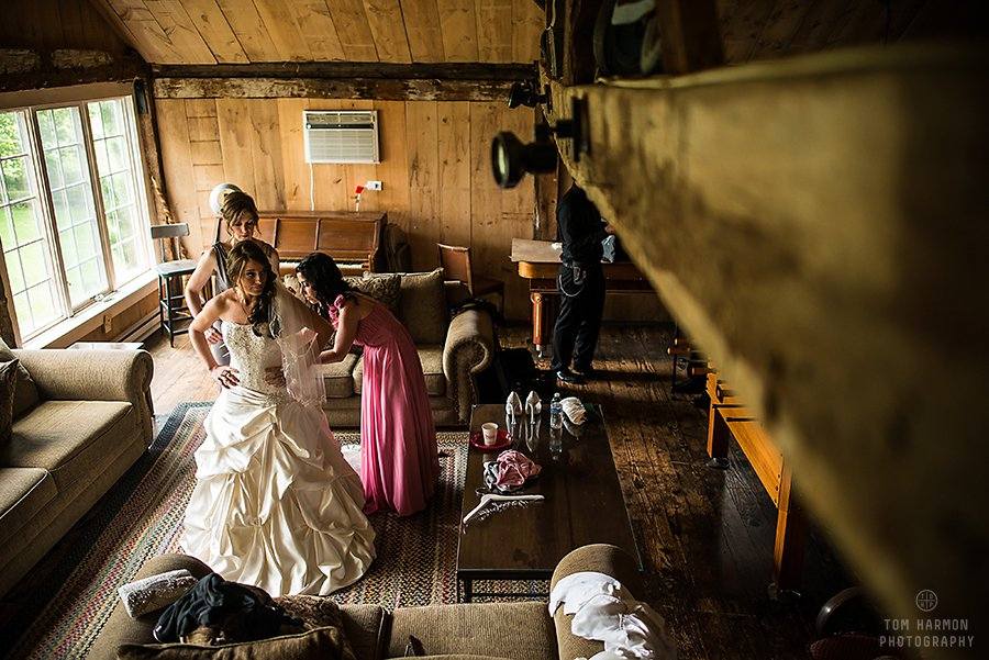 bride getting her dress on in the Crist Mill Playhouse